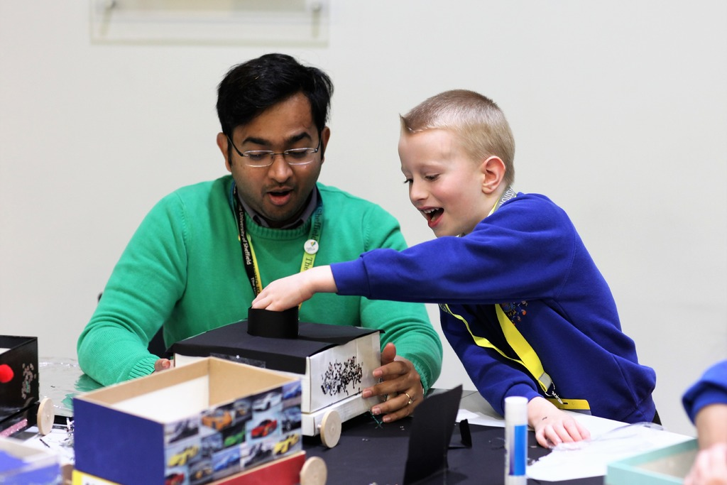 One of the pupils from Dinnington Community Primary works on his engineering skills building and decorating a shoebox car with AMRC STEM Ambassador and Great British Bake Off winner Rahul Mandal.