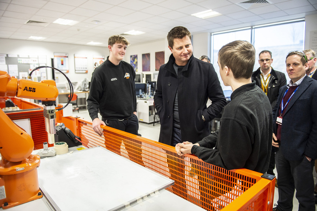 AMRC Training Centre apprentices give a robotics demonstration to George Clarke, programming the robot to write out 'Welcome George'.