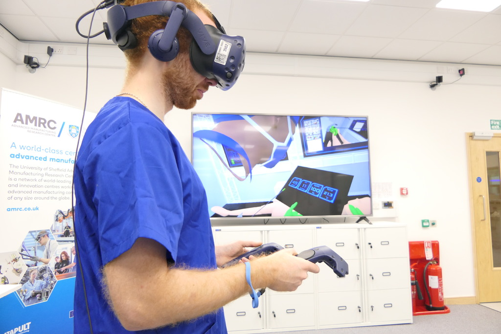 Project engineer Rob Stacey wears a virtual reality headset with his avatar in the Digital Operating Theatre shown on the screen behind him.