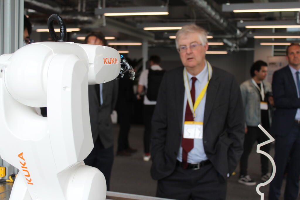 First Minister of Wales, Mark Drakeford, studies a KUKA robot.